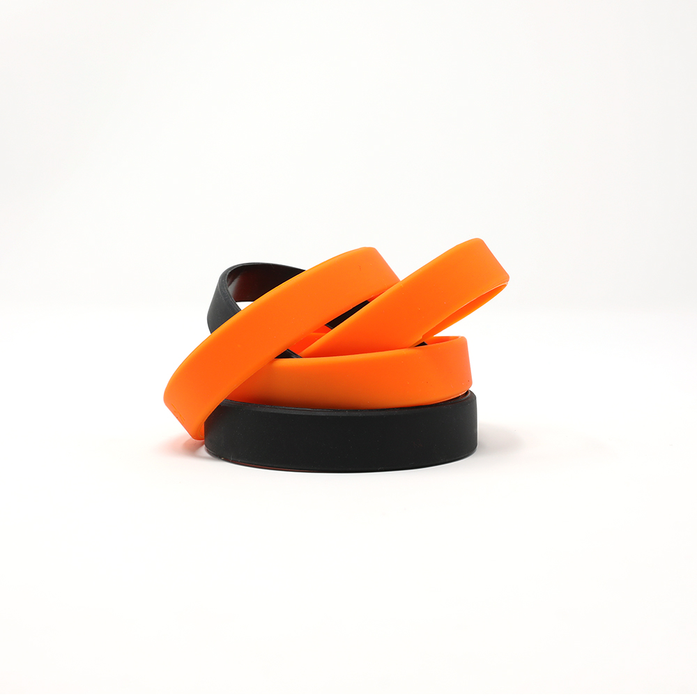 Stack of black and orange blank wristbands.
