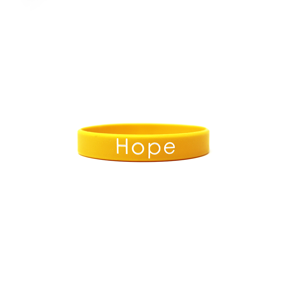 A yellow printed wristband that says hope.