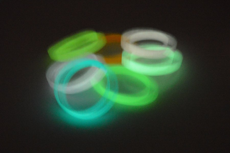 A stack of silicone wristbands that glow in the dark.