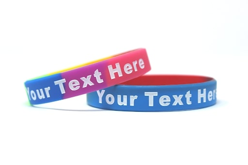 Rainbow colored wristband with the message your text here.