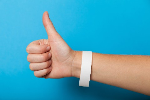 Hand on blue background making thumbs up gesture and wearing a white wristband.